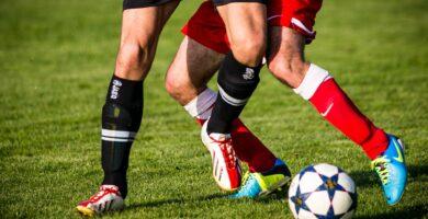 dos jugadores disputando el balón en el terreno de juego