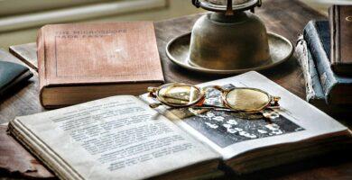 Escritorio con un libro de novela histórica y unos lentes