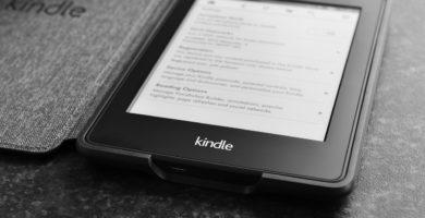 Dispositivo Amazon Kindle para leer ebooks colocado en un soporte negro.